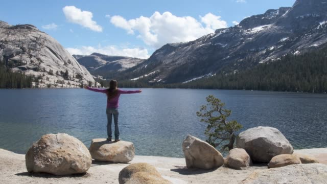 Arms raised solo female traveler enjoying sunshine by secluded lake in spring
