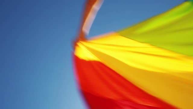 Arms Waving Rainbow Flag Against Sunny Sky