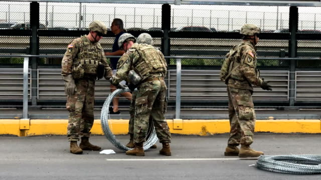 US Army active duty troops from Ft Riley Kansas 97th MP Battalion install protective wire at the international bridge with Mexico on November 2 2018...
