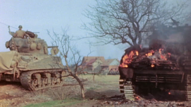 vídeos de stock, filmes e b-roll de s army advancing past burning german army panzer tank with jeep and m4 sherman tank passing by during world war ii european campaign / germany¬† - wehrmacht