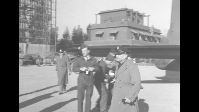 US Army Air Forces Lt Gen Ira Eaker deplanes walks on airfield and is greeted by military personnel / CU Eaker / 2shot British Air Chief Marshal Sir...