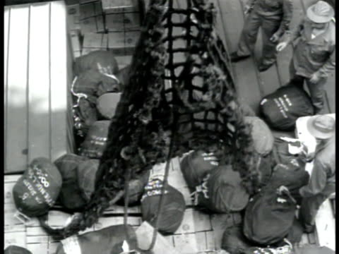Army ASF Soldiers dumping duffle sacks into ship's cargo hold on top of boxes of supplies Above below wrapped airplane being lowered by crane into...