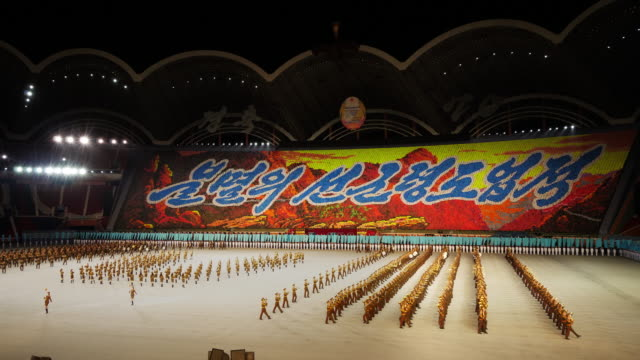 army band marching and performing in amazing formation choreography during mass games in pyongyang, north korea, dprk. wide shot - spoonfilm stock-videos und b-roll-filmmaterial