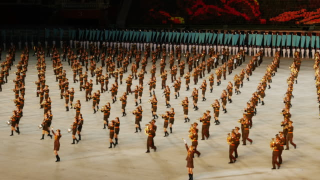 TL Army Band marching and performing in amazing formation choreography during Mass Games in Pyongyang North Korea DPRK Medium shot