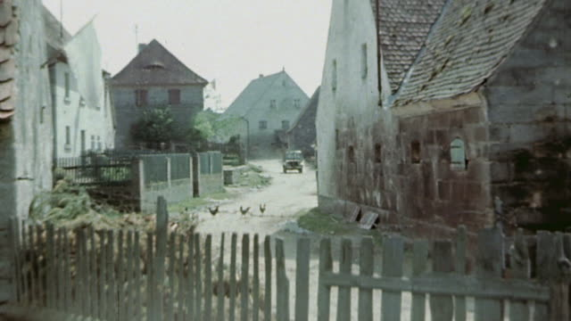 vidéos et rushes de s army convoy driving fast through small village / germany - 1945