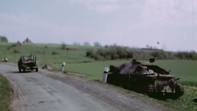 vidéos et rushes de army convoy driving past wrecked german tank on country road / germany - 1945