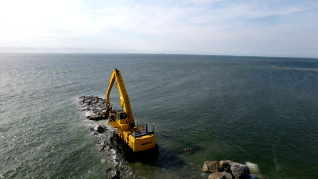 vídeos de stock e filmes b-roll de army corps of engineers rebuild a jetty in point lookout, ny aerial view - pontão