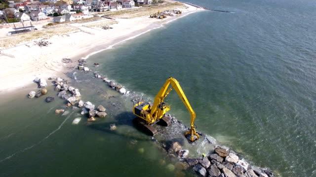 vídeos de stock, filmes e b-roll de army corps of engineers rebuild a jetty in point lookout, ny aerial view - equipamento de construção