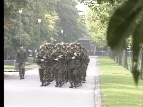 deepcut barracks investigation criticised; tx england: surrey: deepcut army barracks: ext soldiers marching along road through barracks, sign at... - surrey england stock videos & royalty-free footage