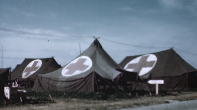 vidéos et rushes de army field medical facility tents in field, jeep and trucks marked with red crosses driving past, patient in camp bed beneath open tent edge - world war 1