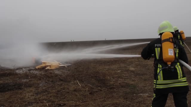 army fire-fighters with the 336th engineer detachment participate in a simulated aircraft fire emergency response exercise with canadian and romanian... - rettungsdienst mitarbeiter stock-videos und b-roll-filmmaterial