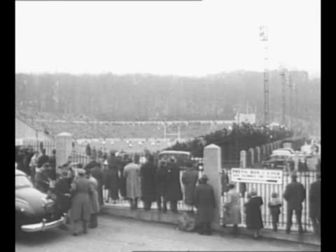 army general maxwell taylor with man at annual army-navy football game / people stand outside fence at stadium, watch game action in background /... - 士官候補生点の映像素材/bロール