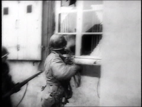US Army infantry advancing through town / Soldiers use wooden ladder to break down door / Soldier holding motion picture camera / Scenes of wounded...