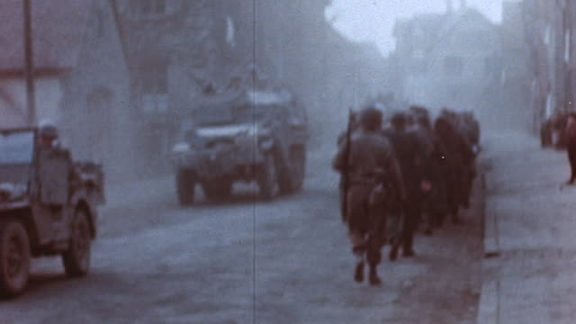 S Army infantry walking by side of village road past parked military Jeep and halftrack / Germany