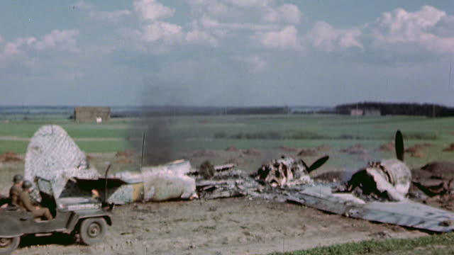 s army jeep driving to and stopping to examine wrecked and smoldering luftwaffe bomber then driving over wreckage and away / germany - explosive stock videos & royalty-free footage