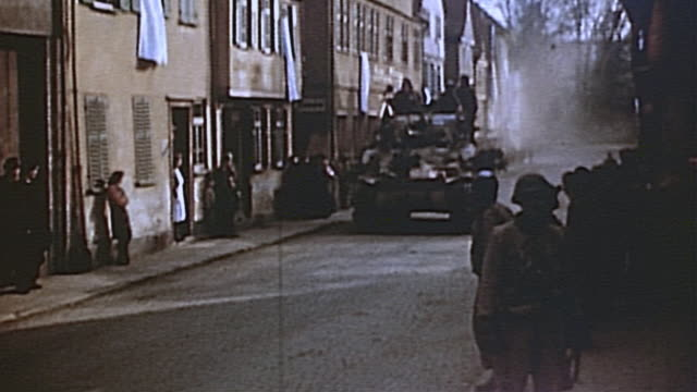 S Army M4 Sherman tank convoy traveling down streets of village with liberated French prisoners cheering at the sides during WWII European campaign /...