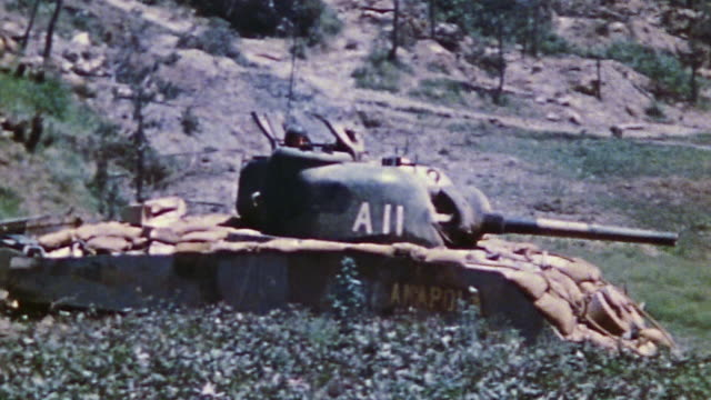 S Army M4 Sherman tanks advancing in open country and firing cannon / Okinawa Japan