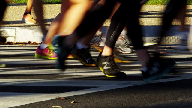 vídeos y material grabado en eventos de stock de u.s. army marathon runners stride across a crosswalk. - paso largo