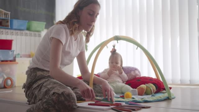 stockvideo's en b-roll-footage met leger moeder boek kleurplaten voor volwassenen en spelen met haar baby. - leger krijgsmacht