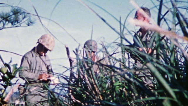 s army officers conferring and soldiers advancing carrying mortars and laying telephone wire / okinawa japan - 迫撃砲点の映像素材/bロール