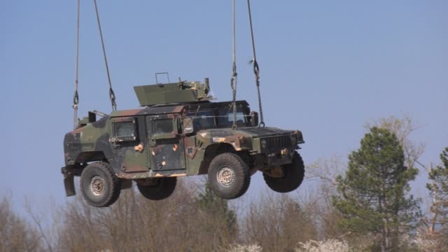 stockvideo's en b-roll-footage met us army paratroopers conduct sling load operations with an armored high mobility multipurpose wheeled vehicle with a ch47 chinook helicopter during... - humvee