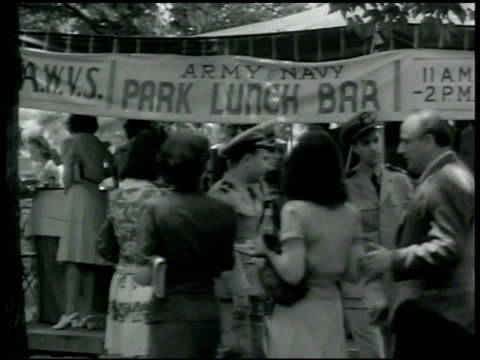 stockvideo's en b-roll-footage met army park lunch bar tent people walking w/ trays sitting at outside tables civilians military men women eating lunch women drinking soda w/ straw - 1942
