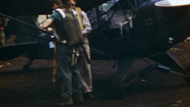 s army pilots gearing up in sidcot suits and preparing piper j3 for takeoff during wwii - military aeroplane stock videos & royalty-free footage
