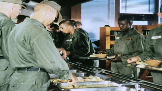vídeos de stock, filmes e b-roll de army recruits being served and eating in mess hall / fort leonard wood missouri united states - campo de treinamento militar