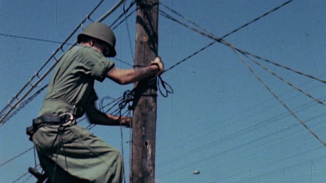 vídeos de stock, filmes e b-roll de s army signal corpsman climbing and descending a telephone pole overlooking camel beach during operation dragoon / saintraphael france - telegraph pole