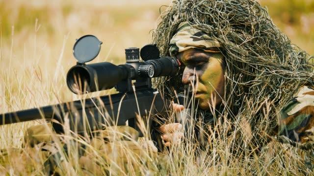 vidéos et rushes de bataille d'opération militaire armée sniper regardant à travers l'étendue dans le domaine - viser