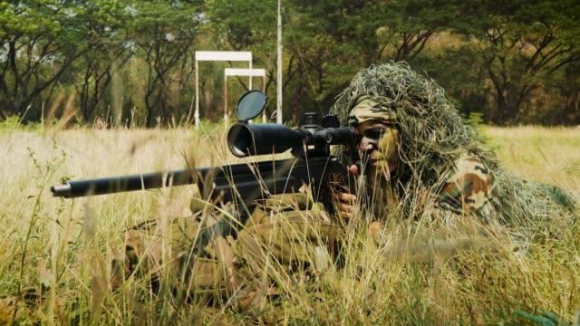 vidéos et rushes de bataille d'opération militaire armée sniper regardant à travers l'étendue dans le domaine - armée