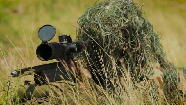 armén sniper militära operation slaget tittar genom omfattningen i fältet - armé bildbanksvideor och videomaterial från bakom kulisserna