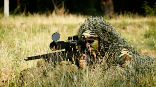 Army sniper military operation battle looking through the scope in the field