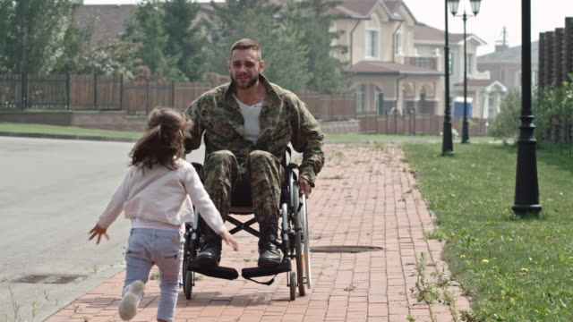 Army soldier in wheelchair embracing little daughter