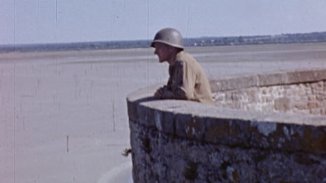 S Army soldier looking down from a wall while locals play on the beach below / Normandy France