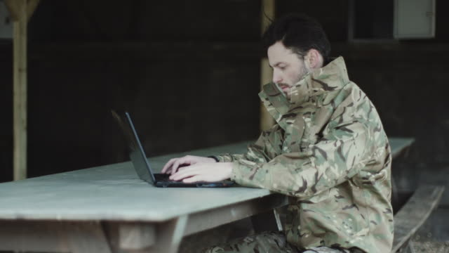 army soldier on laptop at base camp - army stock-videos und b-roll-filmmaterial