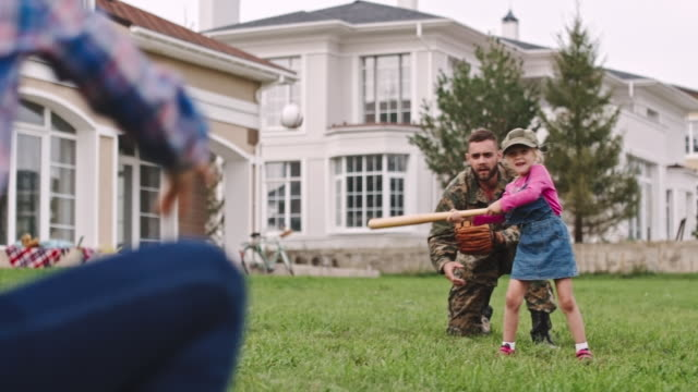 Army soldier playing baseball with family