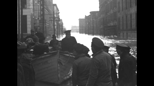 stockvideo's en b-roll-footage met us army soldier unloading box of typhoid serum from us army plane and carrying box to car / two shots of flood victims riding in coast guard boats... - drinking health 1930 film