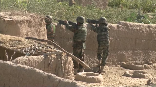 army soldiers aiming and firing their guns from ditch during war in afghanistan - war or terrorism or military点の映像素材/bロール