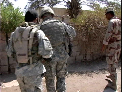 army soldiers and civilians entering gate / mahmudiyah iraq / audio - 言語翻訳点の映像素材/bロール