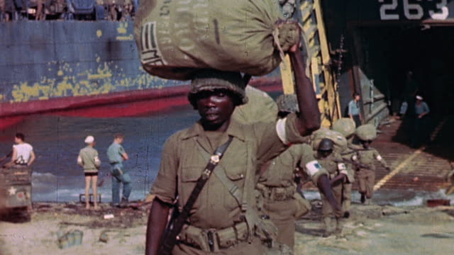 vidéos et rushes de army soldiers carrying barrack bags and other supplies from open bow doors of beached lst, and running back aboard for more / france - soldat