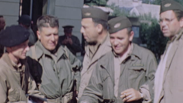 army soldiers conversing in a street, one waving the tricolor flag / normandy, france - 談笑する点の映像素材/bロール