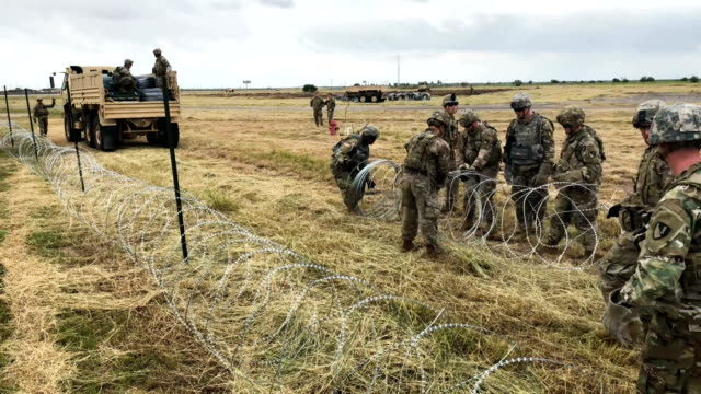 us army soldiers from ft riley kansas string razor wire near the port of entry at the usmexico border on november 4 2018 in donna texas president... - barbed wire stock videos & royalty-free footage