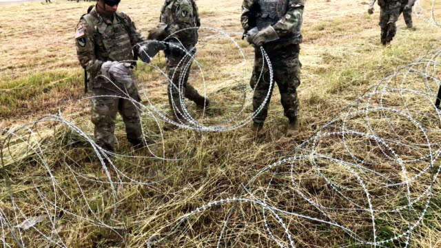 US Army soldiers from Ft Riley Kansas string razor wire near the port of entry at the USMexico border on November 4 2018 in Donna Texas President...