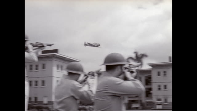 ws pan army soldiers holding rifle and aiming on wwii fighter plane / united states - 真珠湾攻撃点の映像素材/bロール