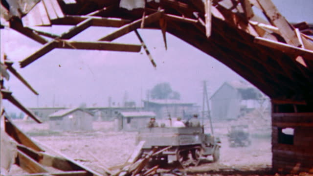 vídeos de stock, filmes e b-roll de s army soldiers in jeep and armored car driving on airfield with wrecked hangar / germany - carro blindado