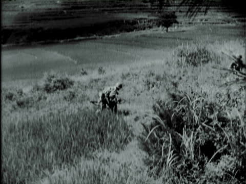 b/w montage u.s. army soldiers kneeling through high grass while advancing through korean countryside and soldiers carrying the wounded and countryside scenes of smoke billowing / korea - korean war stock videos & royalty-free footage