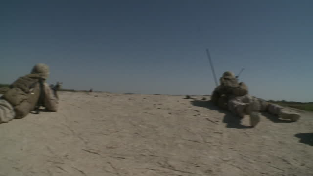army soldiers lie on ground and aim their guns during war in afghanistan - war or terrorism or military点の映像素材/bロール