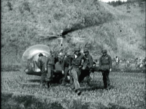 MONTAGE US Army soldiers loading wounded soldier on to waiting Bell H-13 Sioux helicopter's side litter, medical team standing with officer gives signal for second helicopter, helicopter coming in for medevac pickup, row of waiting ambulances / Korea