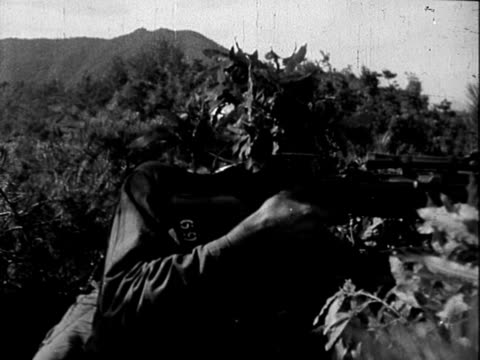 US Army soldiers patrolling dirt road in Korea / camouflaged US Army soldier firing M1 Garand rifle with telescopic sight / US soldiers kneeling in...
